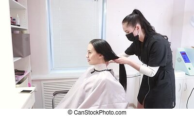 Attractive young woman stylist dresses client with hairdressing peignoir. Hairdresser in a protective face mask