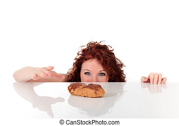Attractive young woman being tempted, ready to take the ?clair from table. Studio shot. White background. shalow dof, focus on eyes