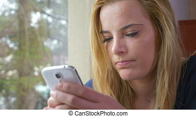 Attractive young woman texting on a smartphone at the window