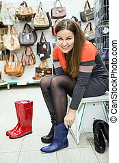 Attractive young woman trying boots