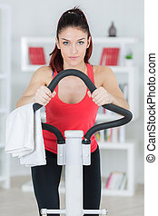 attractive young woman using a step machine indoors