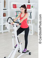 attractive young woman using a step machine