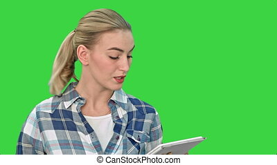Attractive young woman using a touchscreen tablet, reading and talking to a camera on a Green Screen, Chroma Key.