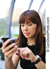 Attractive young woman using her pda