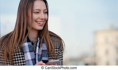 Attractive young woman using her smartphone and smile in the street.