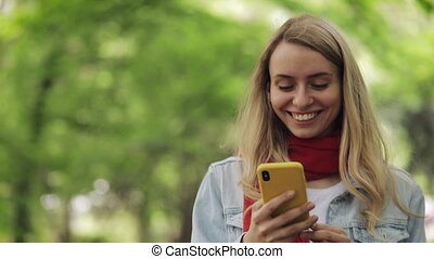 Attractive young woman using smartphone walking down the park. Spring or summer time.