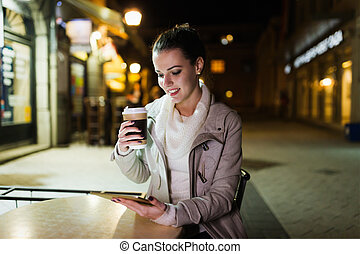 Attractive young woman using tablet in cafe