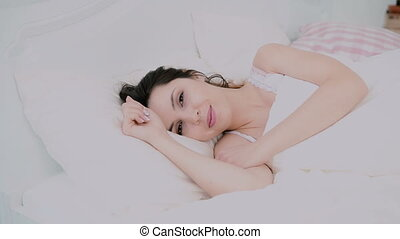 Attractive young woman waking up in bed at home. Girl looks to camera and cute smiles. Fresh and happy woman in morning.