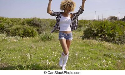 Attractive young woman walking in a meadow
