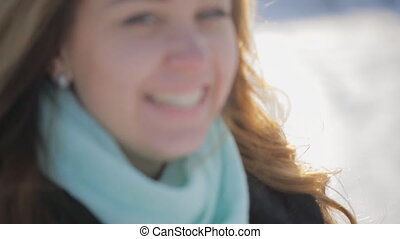 Attractive young woman walking in snowy winter, laughing