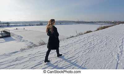 Attractive young woman walking in snowy wintertime outdoors. Happy female has fun at beautiful sunny day, walks, enjoys nature, takes thermos in hands in Russian winter. Nice lady with brown wavy hair in black fur coat, trousers, high boots on bank of frozen river on snow scenery. On background ...