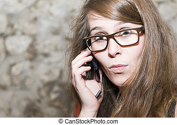 Attractive young woman wearing glasses reacting in surprise to the conversation on a mobile, natural expression with copysapce
