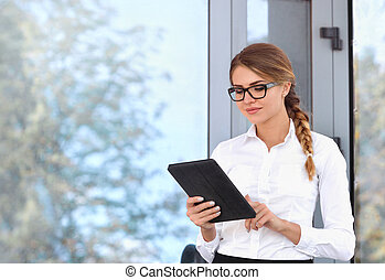 Attractive young woman wearing glasses reading her touchscreen tablet