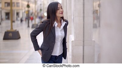 Attractive young woman window shopping in town