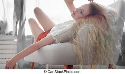 Attractive young woman with a long blond hair lies on a sofa in her living room and using smartphone