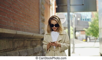 Attractive young woman with blond hair wearing trendy coat and sun glasses is using smart phone walking in modern city. People, modern technology and youth concept.