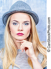 Attractive young woman with blonde hair wearing hat.