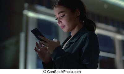 Attractive young woman with cellphone chatting. Dark evening...