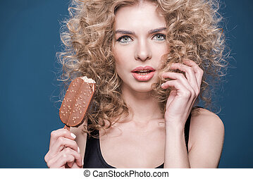 Attractive young woman with curly hair holding ice cream and looking at camera