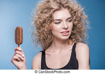 Attractive young woman with curly hair holding ice cream and looking away