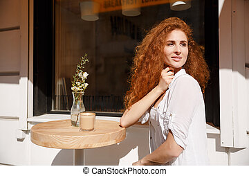 Attractive young woman with curly hair sitting at the table
