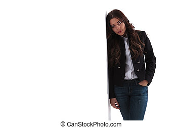 attractive young woman with hand in pocket leaning on wall