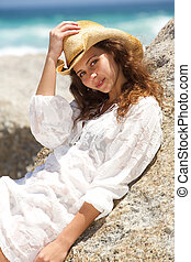 Attractive young woman with hat leaning against rock at the beach