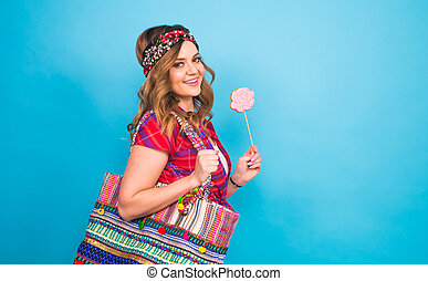 attractive young woman with lollipop in hand on blue background with copy space