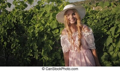 Attractive young woman with long blond hair spends time in vineyards
