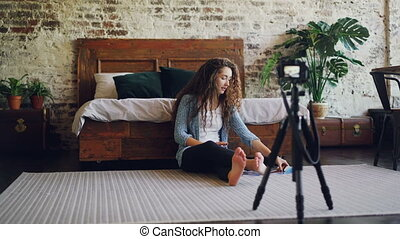 Attractive young woman with long curly hair blogger is recording video for her internet blog using camera, girl is showing smartphone and photographs and talking.