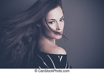 attractive young woman with long dark hair in motion studio shot