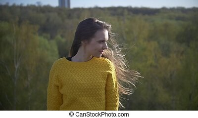 Attractive young woman with long hair standing on the hill...