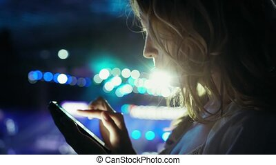 Attractive young woman with long hair writes message using a smartphone and smiling on the background of twinkling neon lights. Side view, close-up