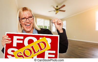 Attractive Young Woman with New Keys and Sold Real Estate Sign In Empty Room of House