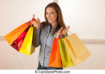 attractive young woman with shopping bags after purchasing in mall