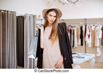 Attractive young woman with shopping bags in clothes shop