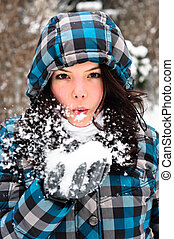 Attractive young woman with snow in her hand