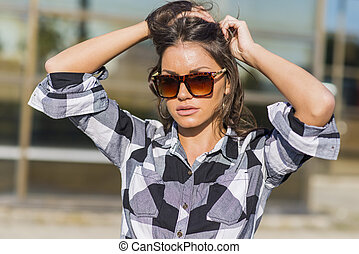 Attractive young woman with sunglasses poses outside