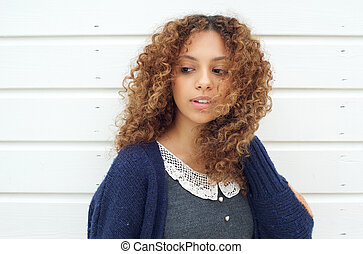 Attractive young woman with wind blowing hair across face