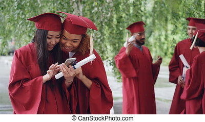 Attractive young women happy graduates are watching photos on smart phone and talking on graduation day while their fellow students are chatting in background.