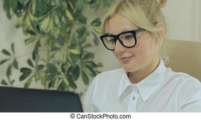 attraente, biondo, donna guardando, a, il, monitor, schermo