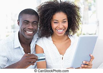 attraente, coppia, usando, tavoletta, insieme, su, divano,...