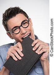 attraktiv, ung man, bitande, book., stilig, manlig, in, blå skjorta, och, glasögon
