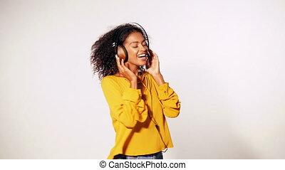 attraktive, african-american, junge frau, hören musik, mit, kopfhörer, und, tanzen, weiß, wand, hintergrund., m�dchen, in, gelber , herbst, top., studio, footage., musik, concept., zeitlupe