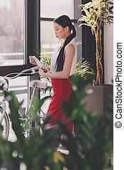 attraktive, asiatisch, geschäftsfrau, arbeitende , mit, digital tablette, in, buero, fahrrad, stehen