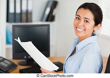 attraktive, frau besitz, a, blatt papier, und, posierend, während, sitzen, büro