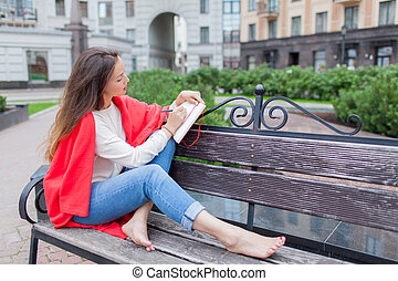 attraktive, m�dchen, sitzen, auf, a, bank, mit, bloße füße, bedeckt, mit, a, rote decke, in, der, neu , wohngebiet, und, schreibt, seine, gedanken, in, a, rotes , notebook., der, städtisch, hintergrund