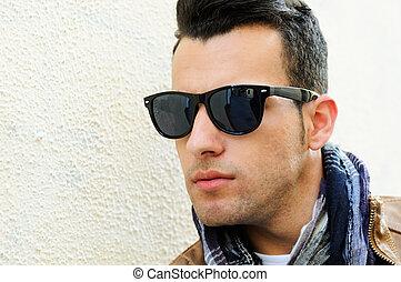 attraktive, mann, tragen, getönte sonnenbrille, in, städtisch, hintergrund