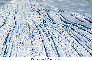 ATV and ski tracks in snow on frosty winter day