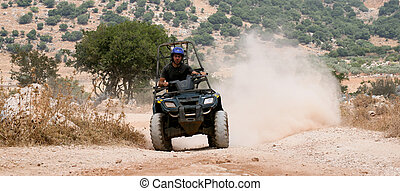 Rider on his four wheel ATV riding over the sand and rocks in the desert